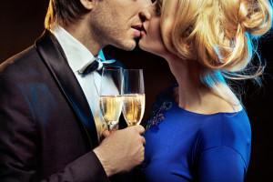 Kissing couple holding glases of a champagne