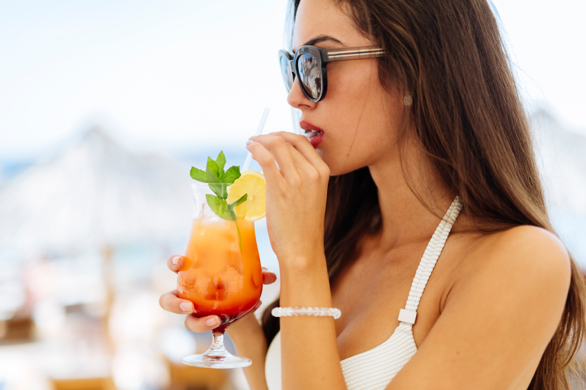 Attractive woman drinking cocktail side portrait